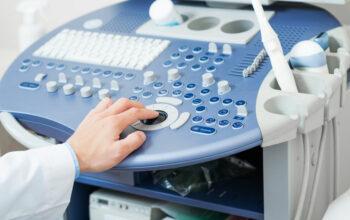 Sonographer using ultrasound machine at work.
