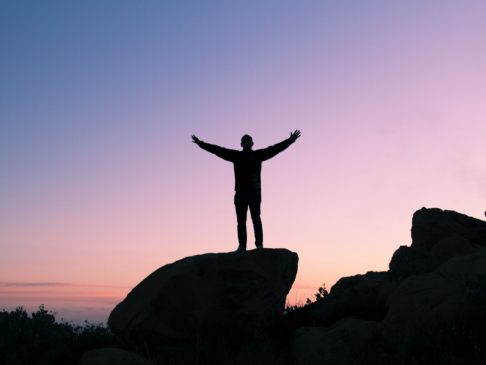 man raising his arms to the sky to express tranquility
